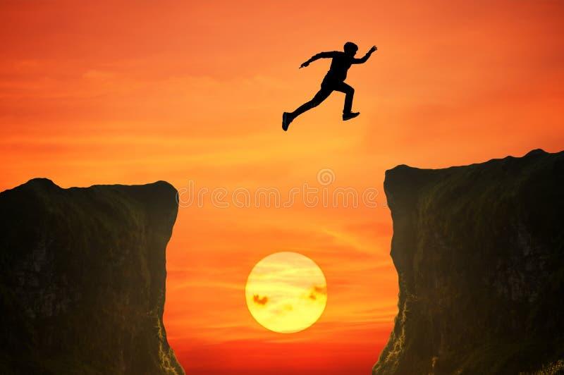 L'uomo che salta sopra la scogliera, siluetta immagini stock libere da diritti