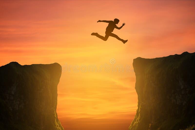 L'uomo che salta sopra la scogliera, siluetta immagini stock