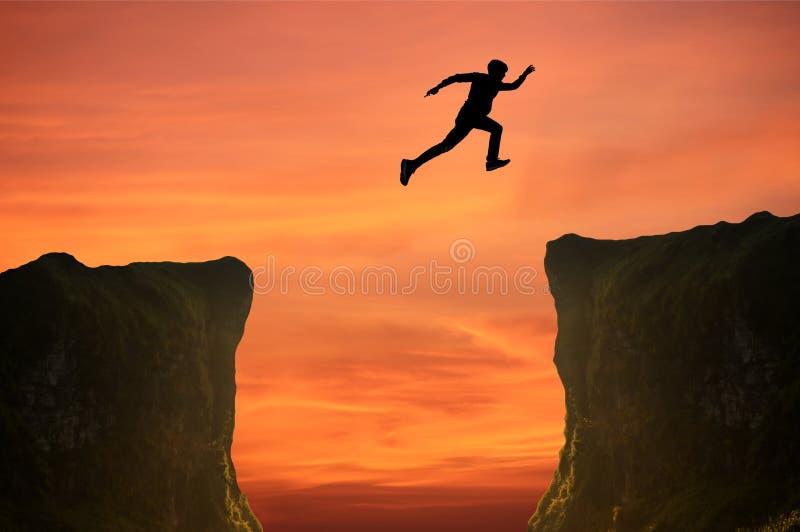 L'uomo che salta sopra la scogliera, siluetta fotografia stock