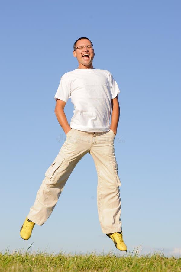 L'uomo che salta sul campo verde immagini stock libere da diritti
