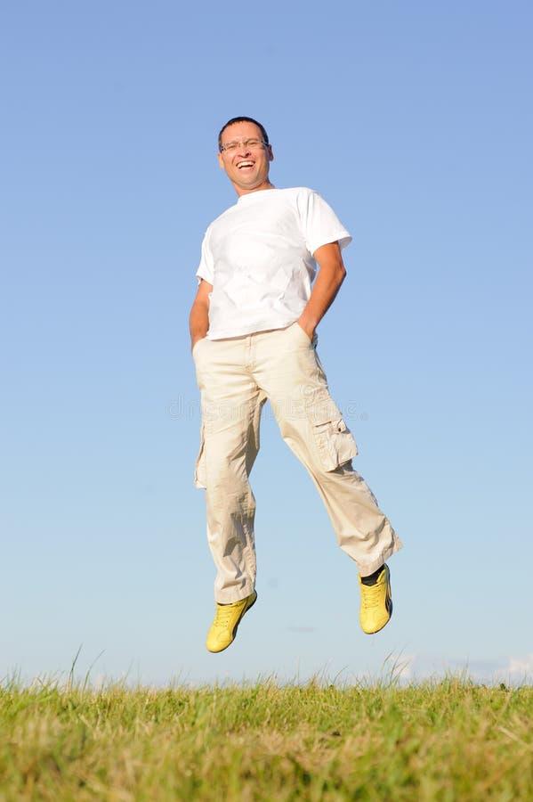 L'uomo che salta sul campo verde immagine stock