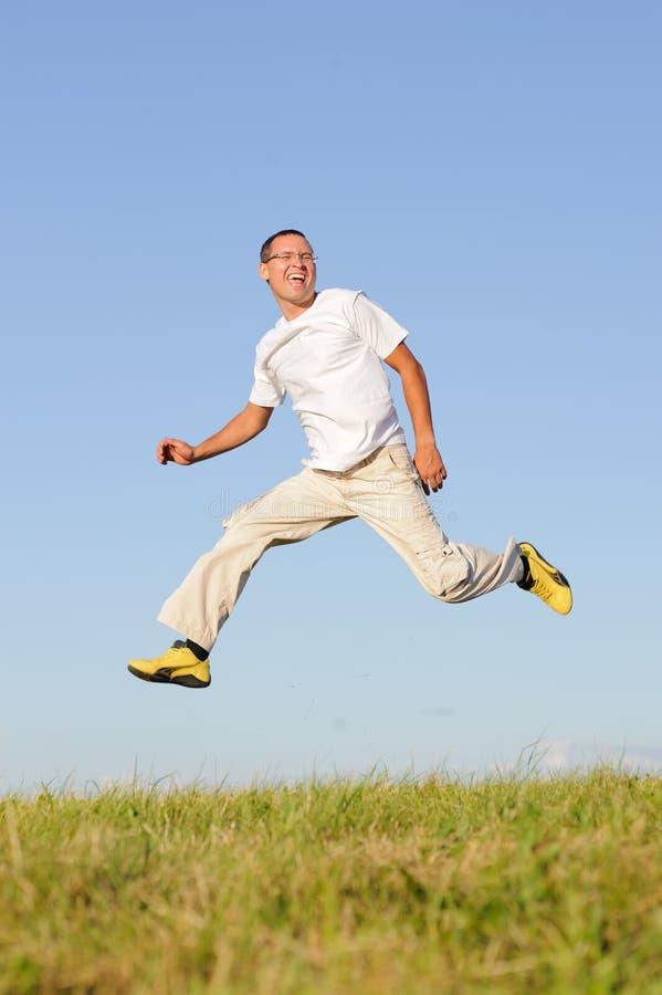 L'uomo che salta sul campo verde fotografia stock