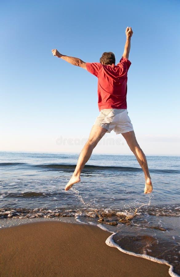 L'uomo che salta sulla spiaggia fotografia stock