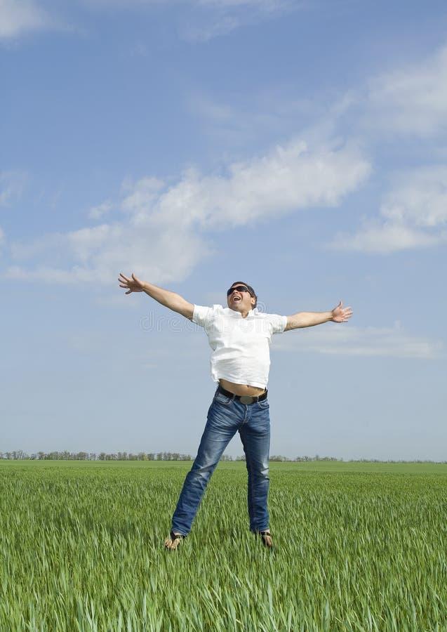 L'uomo che salta un campo verde di erba immagini stock