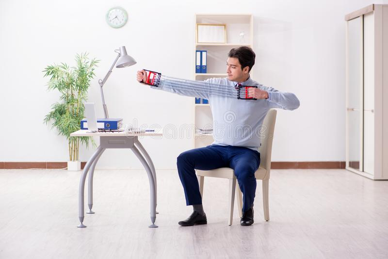 L'uomo che si esercita con la banda elastica in ufficio durante l'intervallo di pranzo fotografie stock libere da diritti