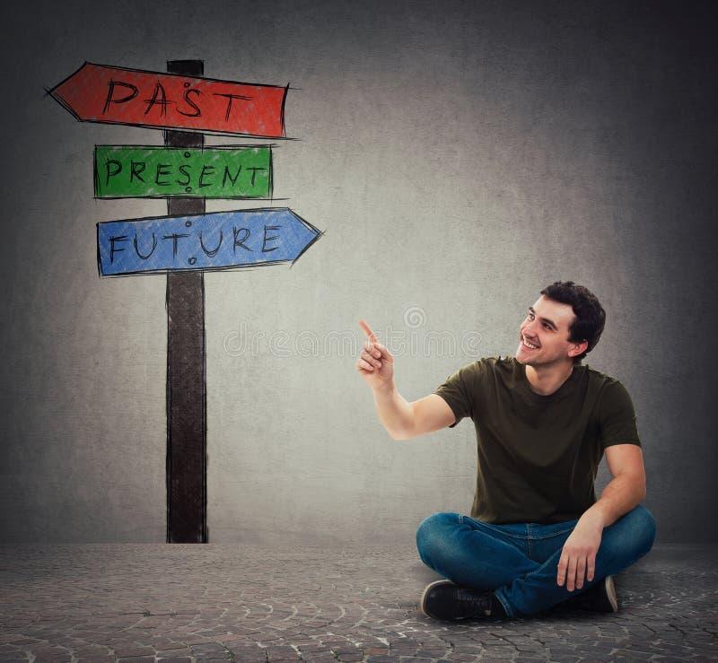L'uomo che si siede sul pavimento che indica l'indice alle frecce del cartello mostra passato, presente e futuro immagini stock libere da diritti
