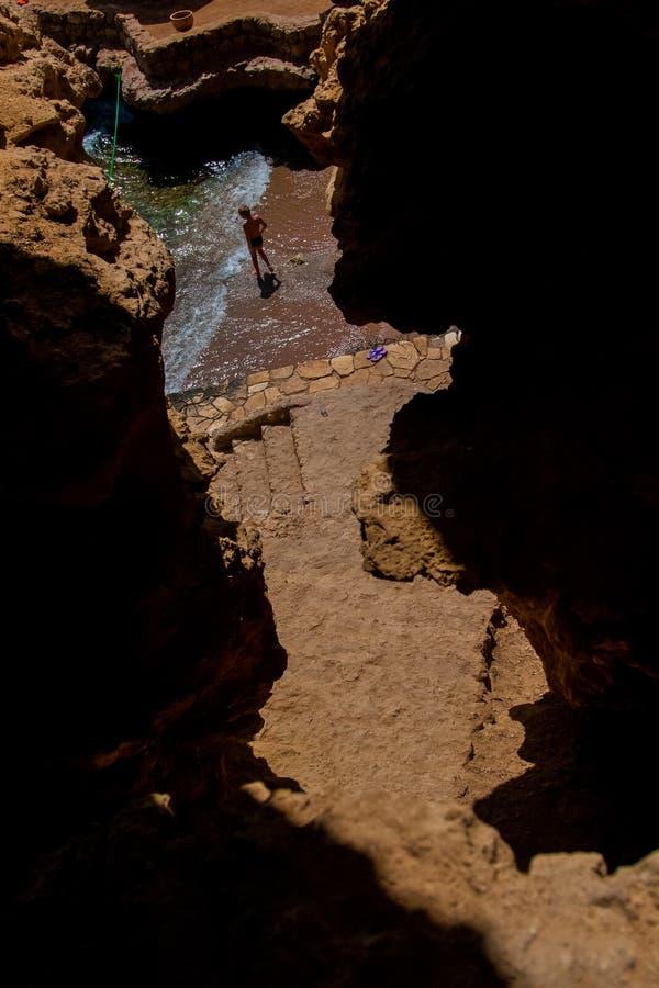 L'uomo che sta nel mare nella baia, la vista dalla cima fotografie stock libere da diritti