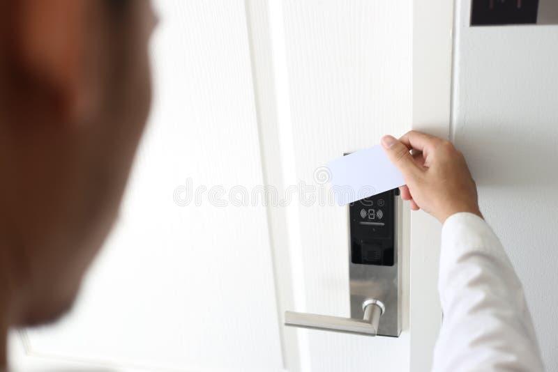 L'uomo che usando il keycard senza contatto per sblocca la porta in hotel immagini stock