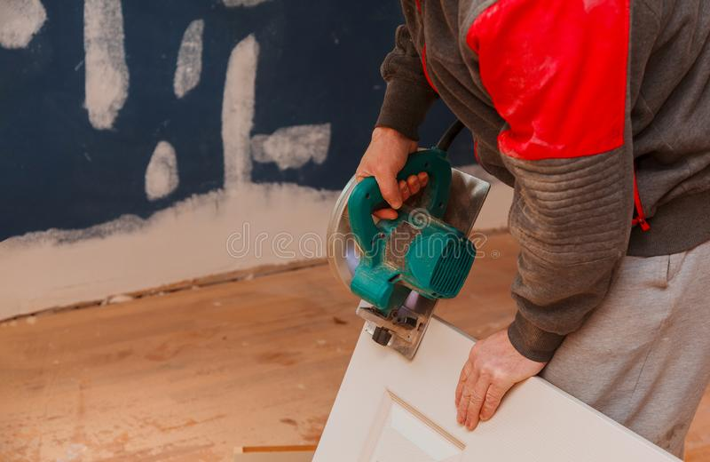 l'uomo che usando una circolare ha visto per il taglio del rinnovamento domestico del legno del costruzione della porta e, strume fotografia stock libera da diritti