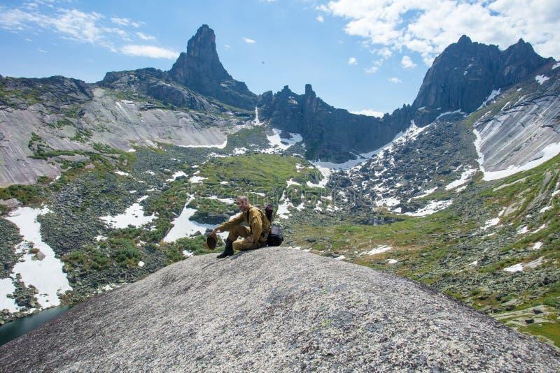 L'uomo in cima alla roccia soddisfa la sete e gode di bello paesaggio immagine stock libera da diritti