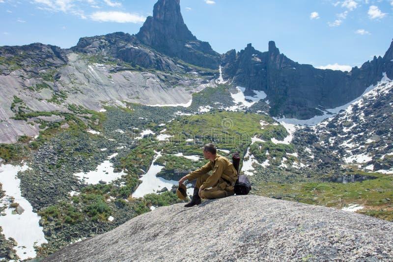 L'uomo in cima alla roccia soddisfa la sete e gode di bello paesaggio fotografia stock libera da diritti
