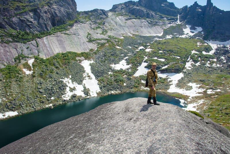 L'uomo in cima alla roccia soddisfa la sete e gode di bello paesaggio fotografia stock
