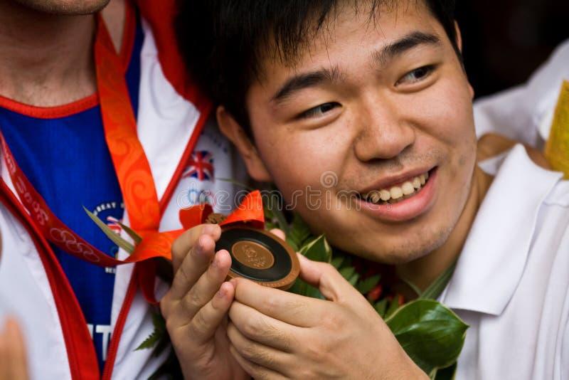L'uomo cinese tiene la medaglia olimpica fotografia stock libera da diritti