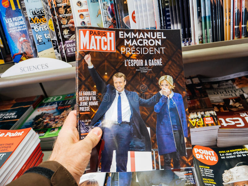 L'uomo compra la rivista di Paris Match con Emmanuel Macron e la sua moglie immagine stock