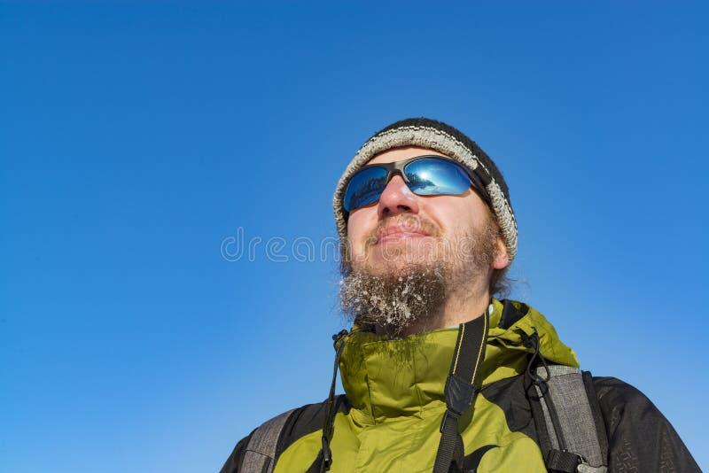 L'uomo con gli occhiali da sole d'uso congelati della barba ed i vestiti dell'inverno guardano immagine stock libera da diritti