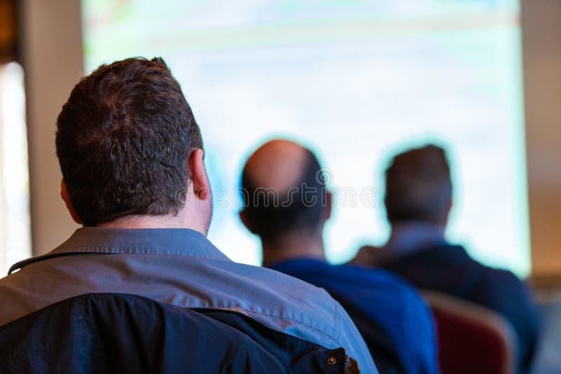 L'uomo con i capelli di scarsità è ad una conferenza immagini stock libere da diritti