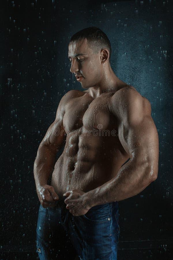 L'uomo con i grandi muscoli ottiene bagnato nella pioggia fotografia stock