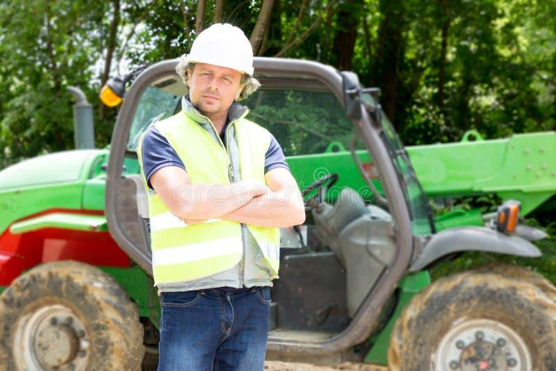 l'uomo con il casco su un cantiere guida una macchina all'aperto immagini stock libere da diritti