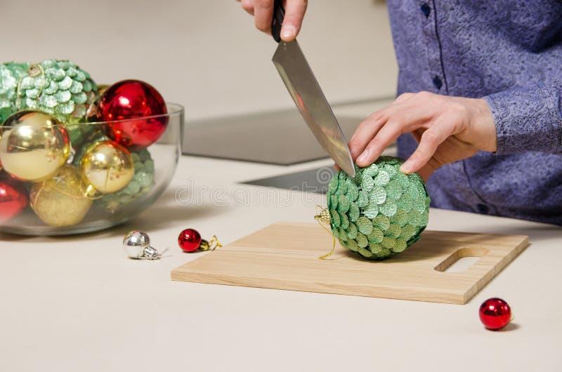 L'uomo con il coltello in sue mani taglia un'insalata delle palle decorate di Natale Concetto della preparazione per la festa mod fotografia stock