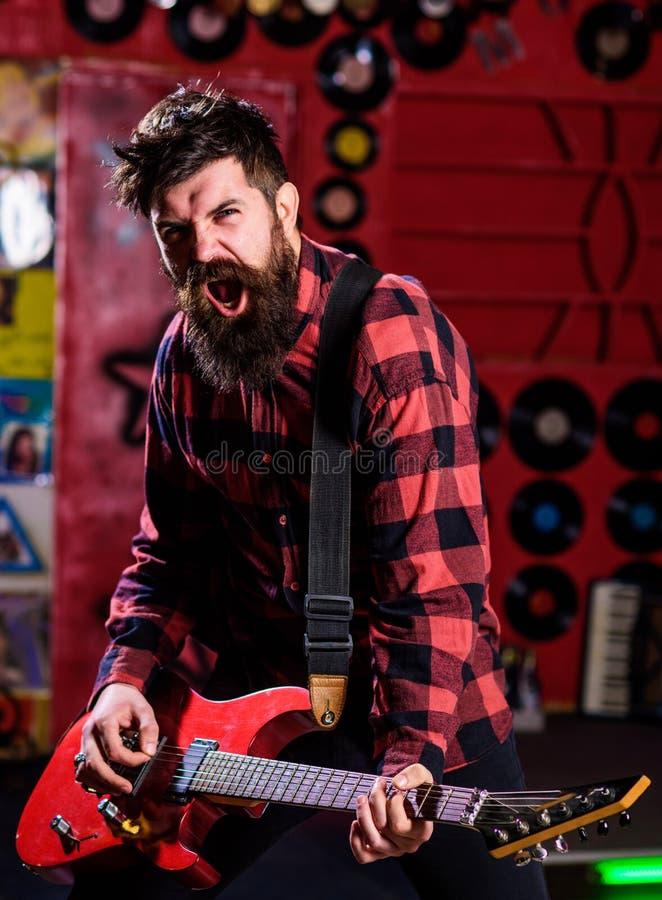 L'uomo con il fronte entusiasta tiene la chitarra, canzone di canto, musica del gioco, immagine stock libera da diritti