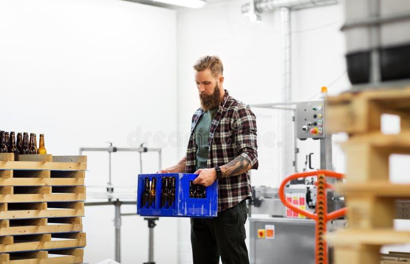 L'uomo con imbottiglia la scatola alla fabbrica di birra della birra del mestiere immagine stock
