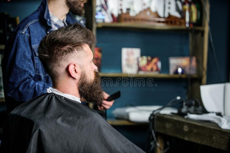 L'uomo con la barba coperta di capo nero si siede nella sedia dei parrucchieri, fondo dei rifornimenti di bellezza Uomo con il cl fotografia stock libera da diritti
