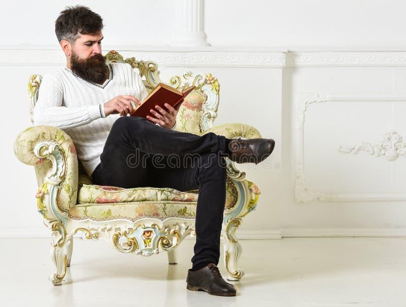 L'uomo con la barba ed i baffi si siede sulla poltrona e sulla lettura, fondo bianco della parete Conoscitore del concetto della  fotografie stock