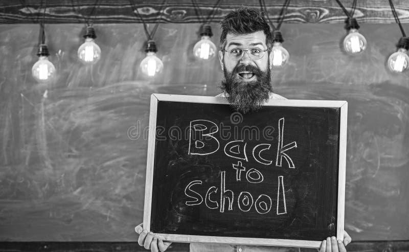 L'uomo con la barba ed i baffi sul fronte felice accoglie favorevolmente i colleghi, lavagna su fondo Concetto di noleggio degli  fotografia stock