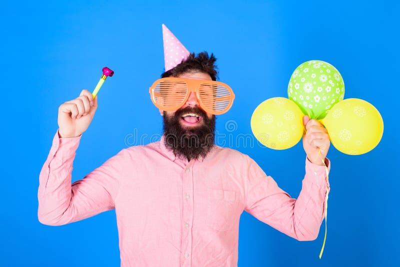 L'uomo con la barba ed i baffi sul fronte felice tiene gli aerostati, fondo blu Concetto del partito Pantaloni a vita bassa in gi immagini stock
