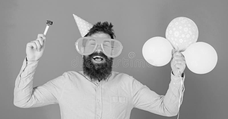 L'uomo con la barba ed i baffi sul fronte felice tiene gli aerostati, fondo blu Pantaloni a vita bassa in occhiali giganti che ce immagini stock