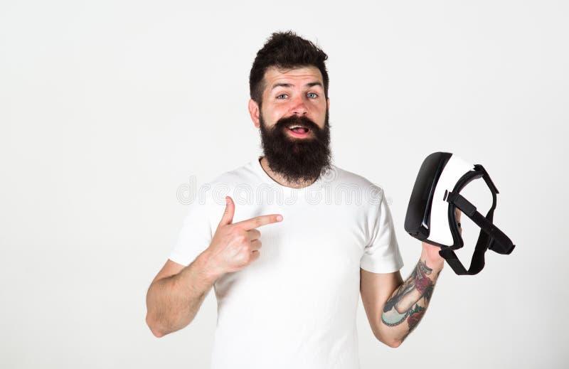 L'uomo con la barba ed i baffi tiene i vetri di VR, fondo bianco Pantaloni a vita bassa sul fronte felice che indicano all'aggegg immagini stock libere da diritti