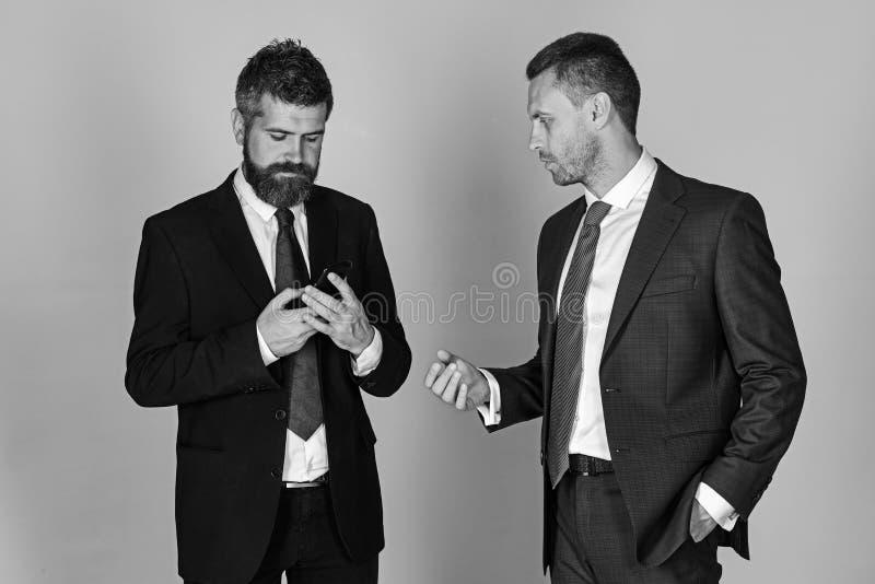 L'uomo con la barba ed il fronte concentrato tiene il telefono immagini stock