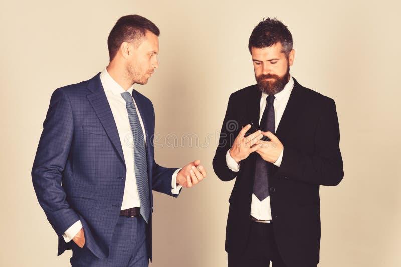 L'uomo con la barba ed il fronte concentrato tiene il telefono fotografia stock libera da diritti