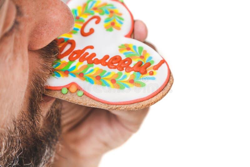 L'uomo con la barba morde il pan di zenzero nella forma di cuore fotografia stock