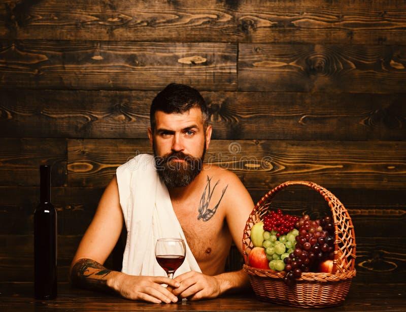 L'uomo con la barba tiene il bicchiere di vino su fondo di legno immagine stock libera da diritti