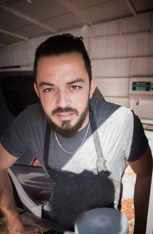L'uomo con la barba tiene lo strumento polising nelle mani nel servizio dell'automobile immagine stock libera da diritti