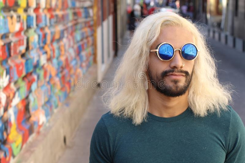 L'uomo con la bionda lunga ha tinto i capelli e gli occhiali da sole freschi fotografia stock libera da diritti
