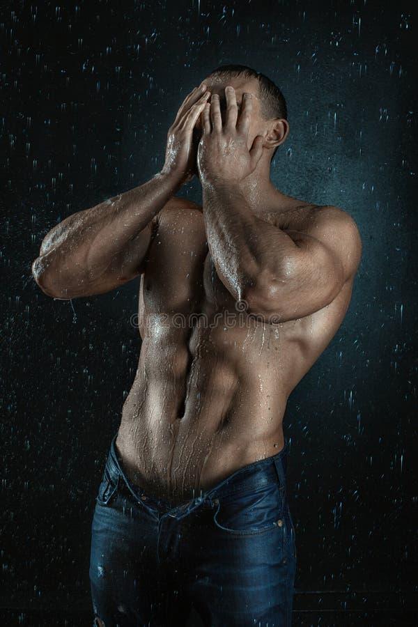 L'uomo con la figura di sport diventa bagnato dalle gocce di acqua immagine stock