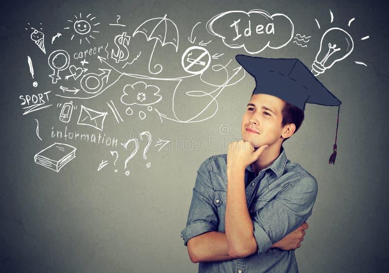 L'uomo con la graduazione che pensa all'istruzione ha molte idee fotografia stock