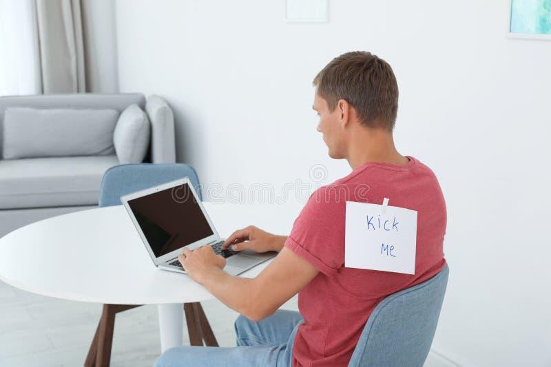 L'uomo con la nota mi DÀ DEI CALCI sulla parte posteriore che funziona con il computer portatile alla tavola all'interno fotografie stock libere da diritti