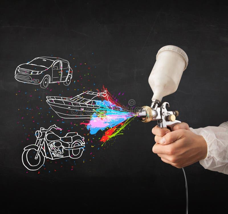 L'uomo con la pittura di spruzzo dell'aerografo con l'automobile, la barca ed il motociclo disegnano fotografie stock