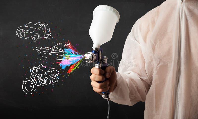 L'uomo con la pittura di spruzzo dell'aerografo con l'automobile, la barca ed il motociclo disegnano immagini stock libere da diritti