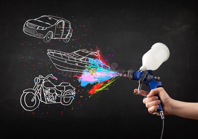 L'uomo con la pittura di spruzzo dell'aerografo con l'automobile, la barca ed il motociclo disegnano immagine stock