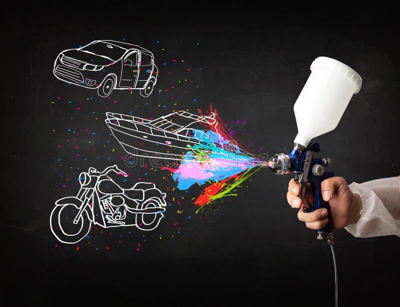 L'uomo con la pittura di spruzzo dell'aerografo con l'automobile, la barca ed il motociclo disegnano fotografie stock libere da diritti