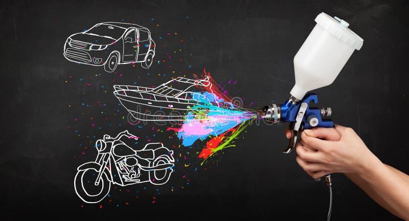 L'uomo con la pittura di spruzzo dell'aerografo con l'automobile, la barca ed il motociclo disegnano immagine stock libera da diritti