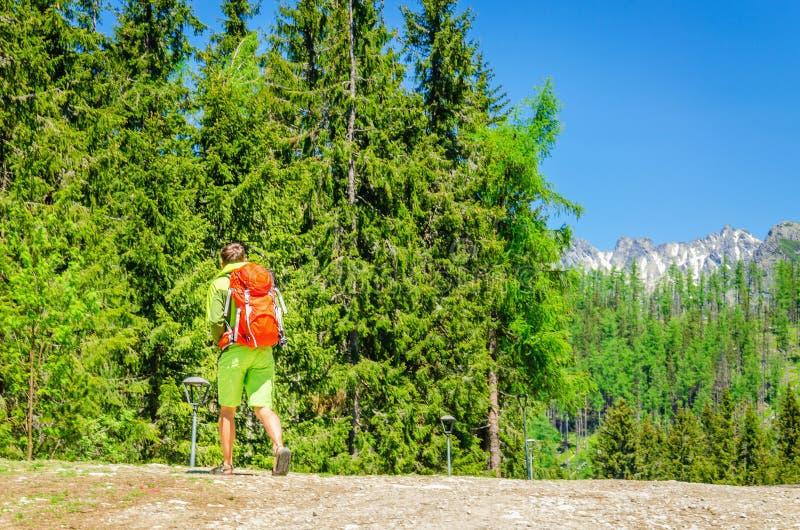 L'uomo con lo zaino arancio cammina in montagne fotografia stock libera da diritti