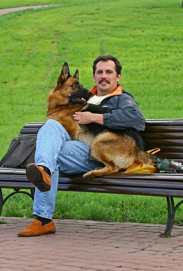 L'uomo con un cane su un banco fotografie stock libere da diritti