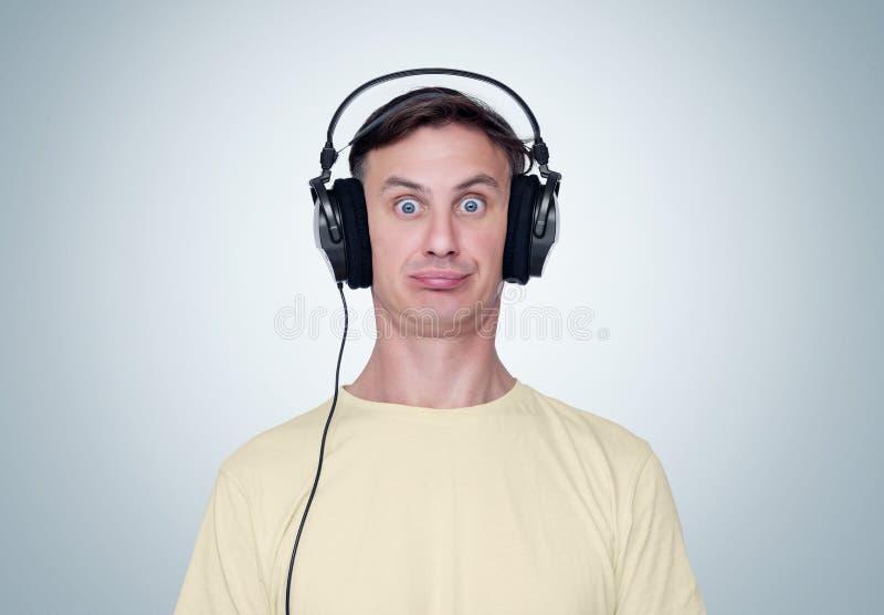 L'uomo con un'espressione sorpresa sta ascoltando musica sulle cuffie, vista frontale fotografia stock