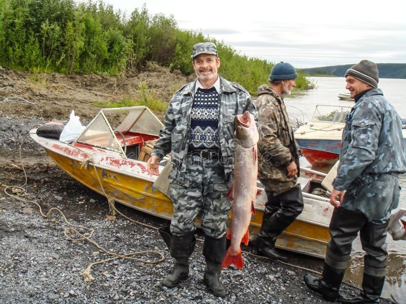 l'uomo con un pesce prende una barca Pesca selvaggia sul fiume immagini stock libere da diritti