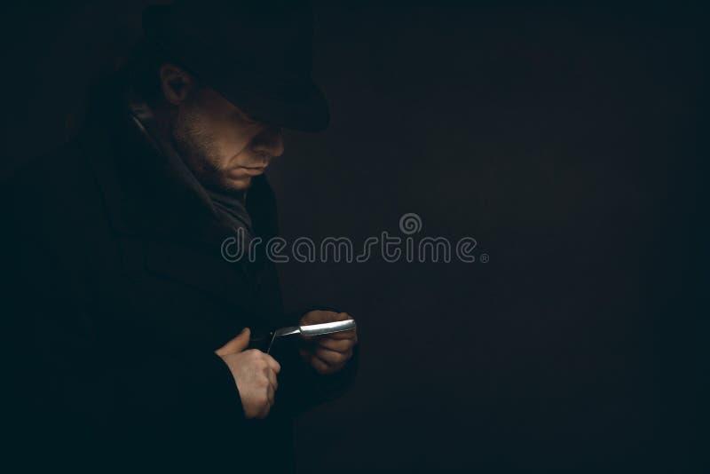 L'uomo con un rasoio sta aspettando nello scuro immagine stock libera da diritti
